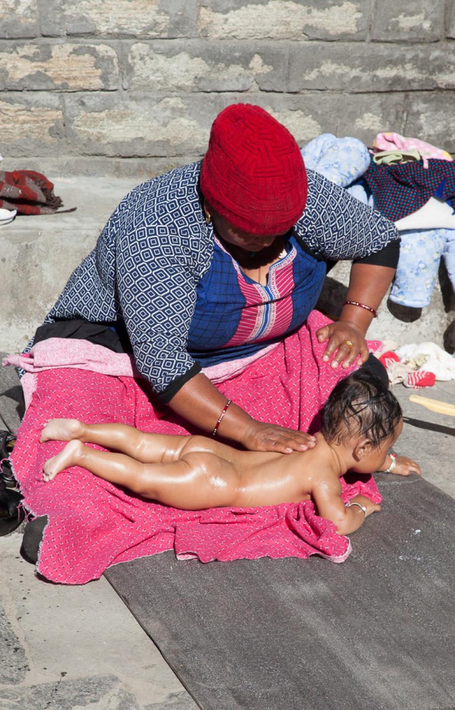 Nepálska matka masíruje po vykúpaní svoje dieťatko. Nie, žiadne chemikálie, natiera ho pravou masťou z jaka. (Pavel Hirax Baričák)